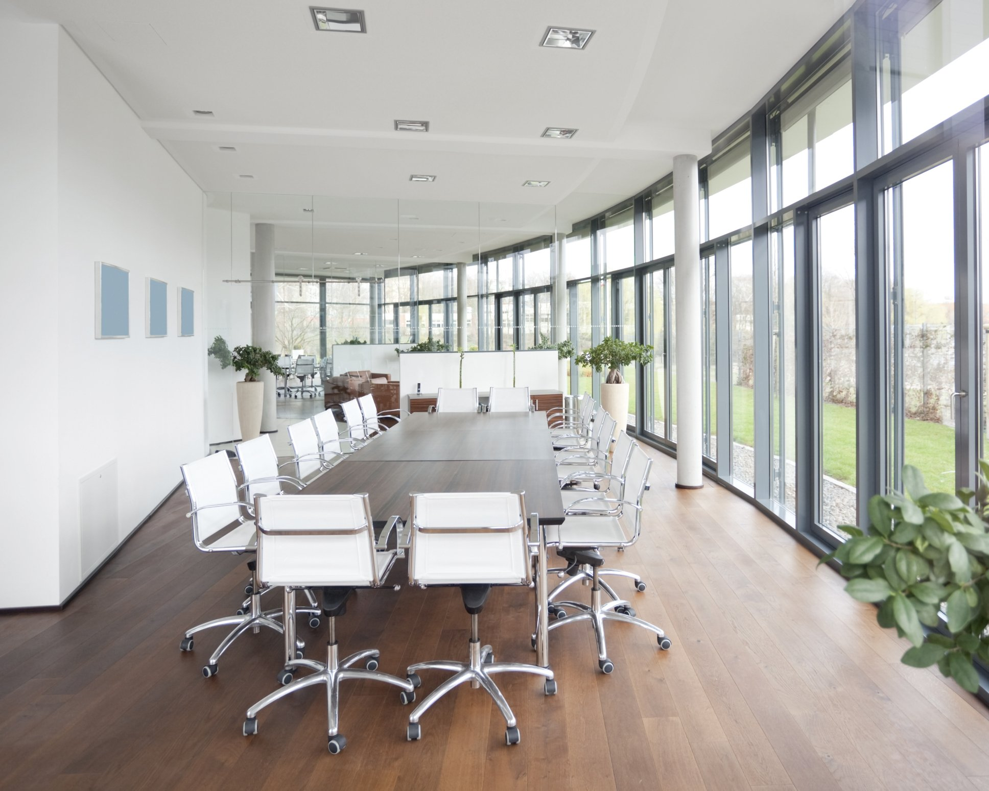 Spacious and bright business conference room with hard wood floor and a bank of windows, opening up into a garden. There are chairs lines up and the decoration is very modern and contemporary.